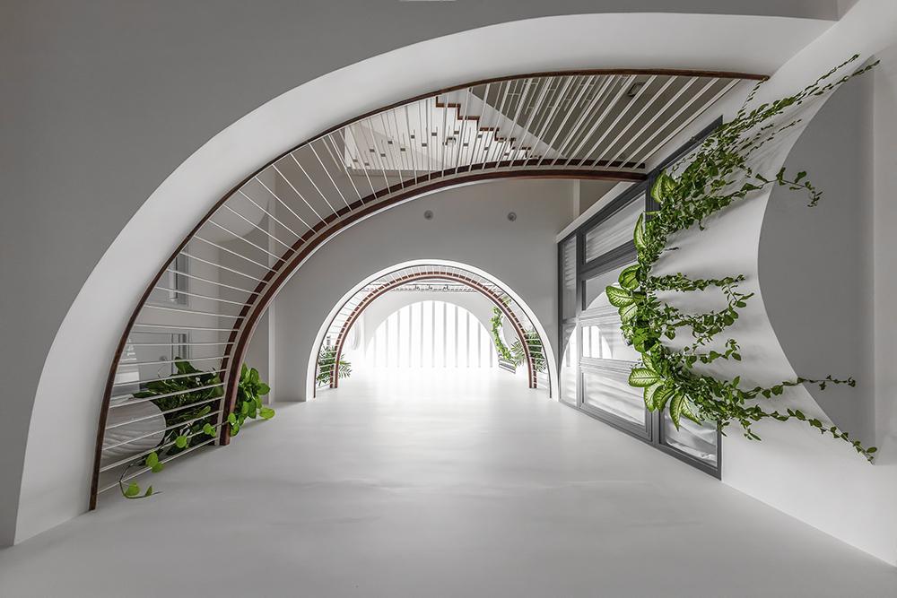 Ở các tầng còn lại, kiến trúc sư thiết kế khoảng thông tầng theo đường cong giúp lấy sáng và gió tự nhiên cho các phòng