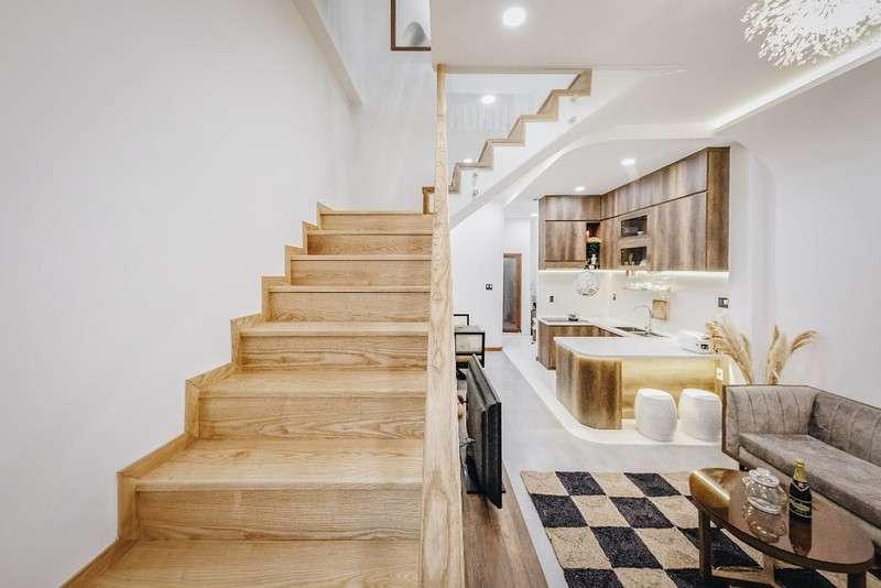 Cầu thang dẫn lên tầng một bằng gỗ có màu sáng.