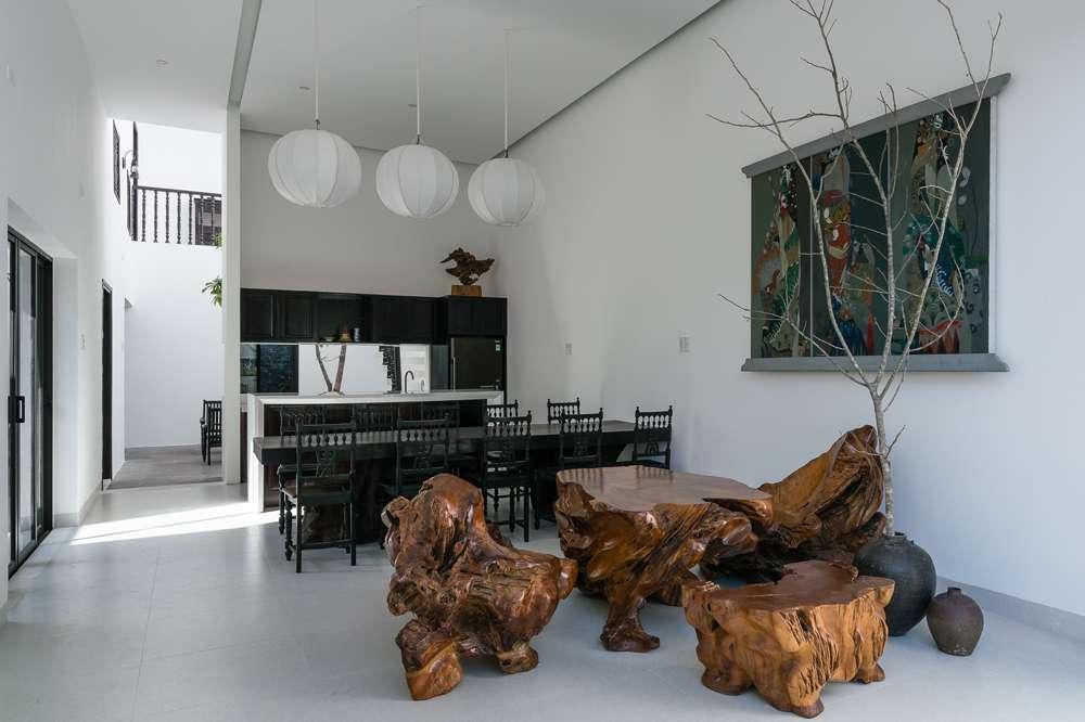 Bộ ghế ở phòng khách là đồ sưu tầm của gia chủ, tạo điểm nhấn bởi màu gỗ lũa nguyên sơ.