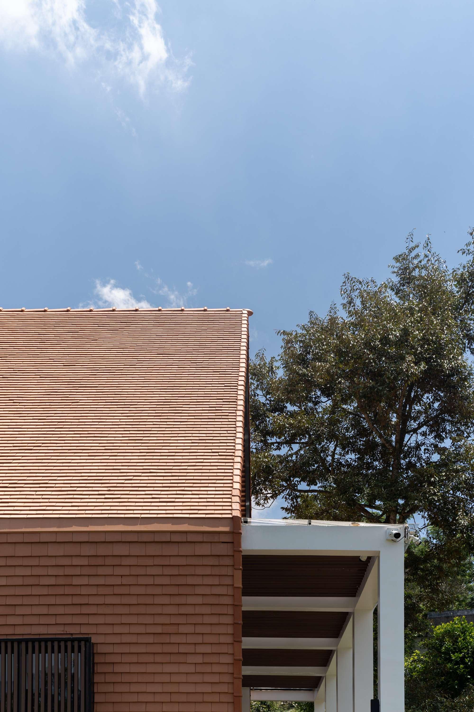 Bên ngoài, mái và tường nhà đều được ốp ngói vảy cá vuông để cách nhiệt.
