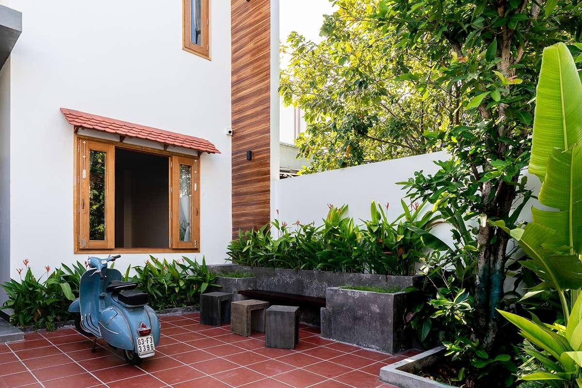 Sân trước Nhà Của Gạo lát gạch nên đỏ đơn giản, trồng nhiều cây xanh và một bộ bàn ghế đá nhỏ