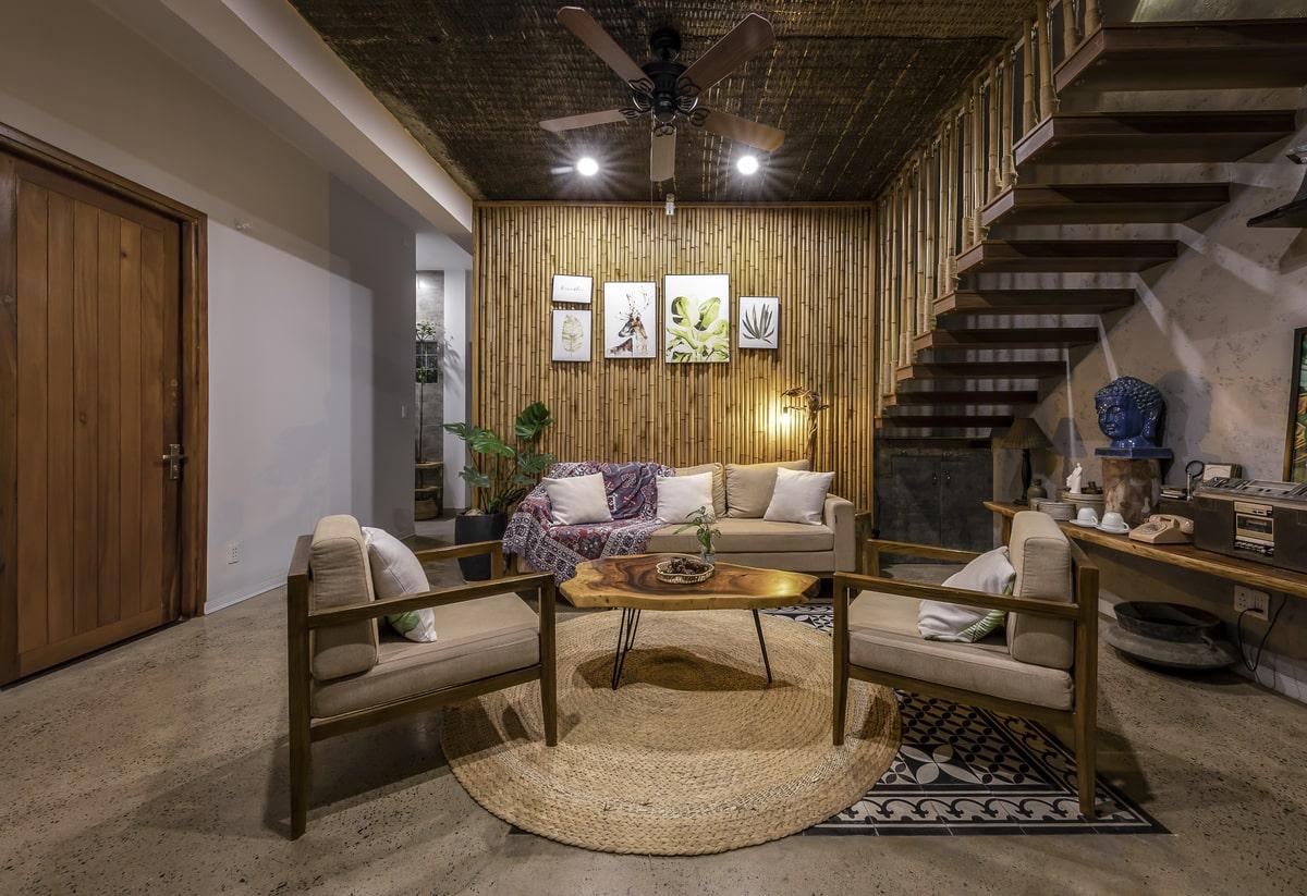 Không gian phòng khách với vách ngăn bằng tre vừa kín vừa hở mang tông trầm tạo sự ấm cúng, mộc mạc và gần gũi