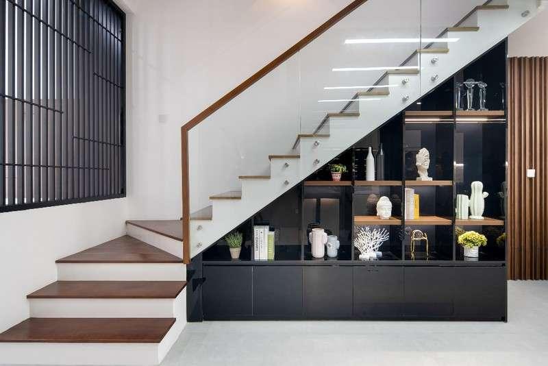 Khoảng trống bên dưới cầu thang, KTS tận dụng làm tủ trang trí vừa tiết kiệm diện tích khiến ngôi nhà bớt trống trải.
